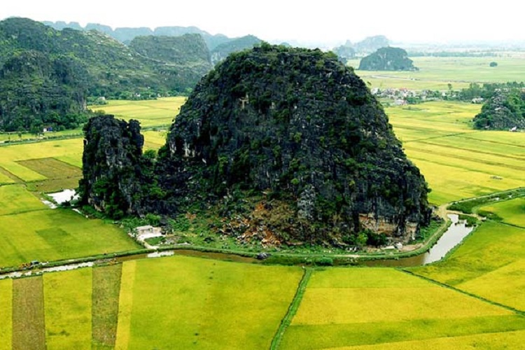 A karst tower stands isolated on the fields